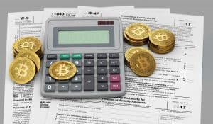Tax forms under a calculator and golden Bitcoins
