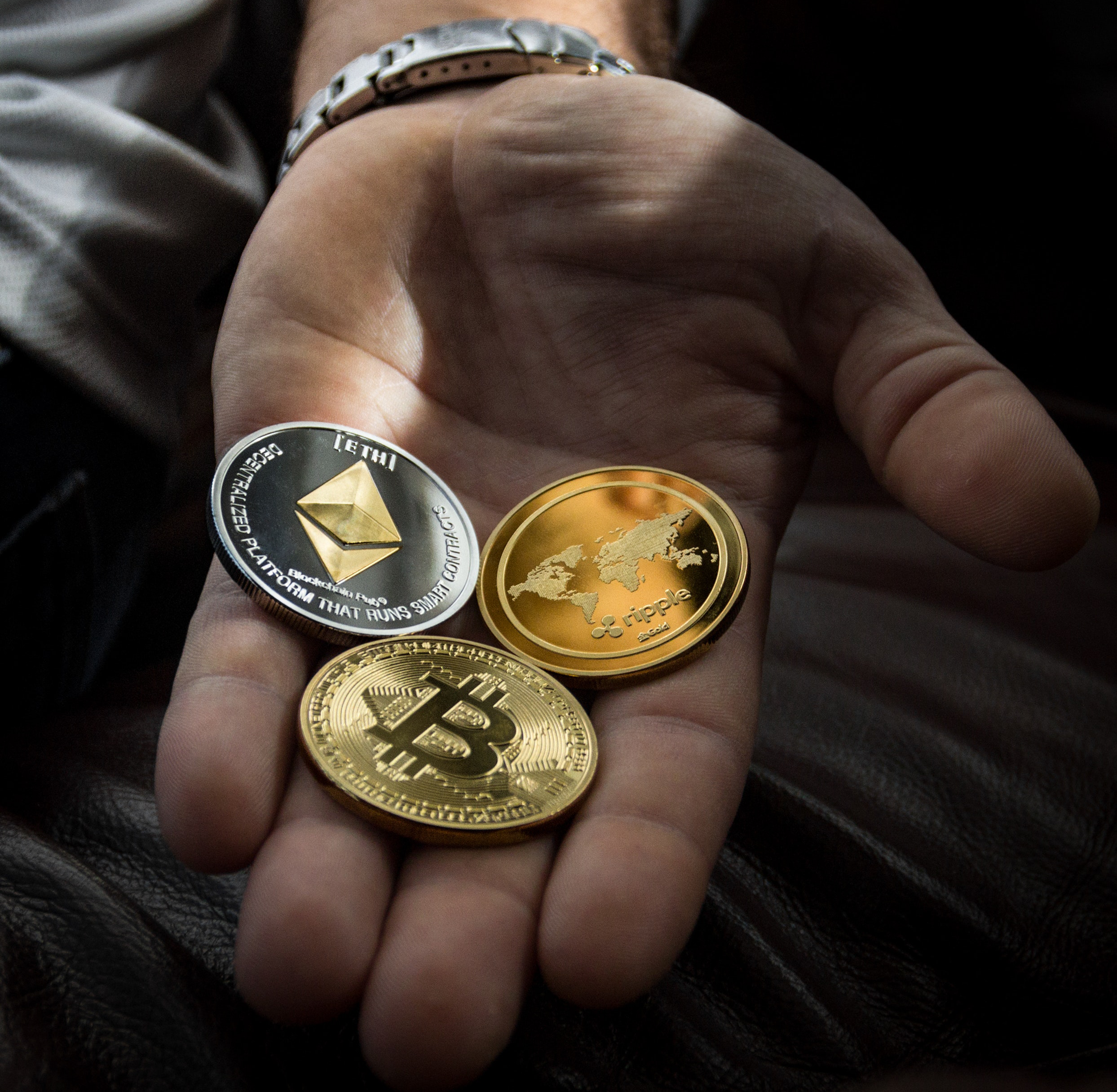 A title image with three different crypto coins on a hand.